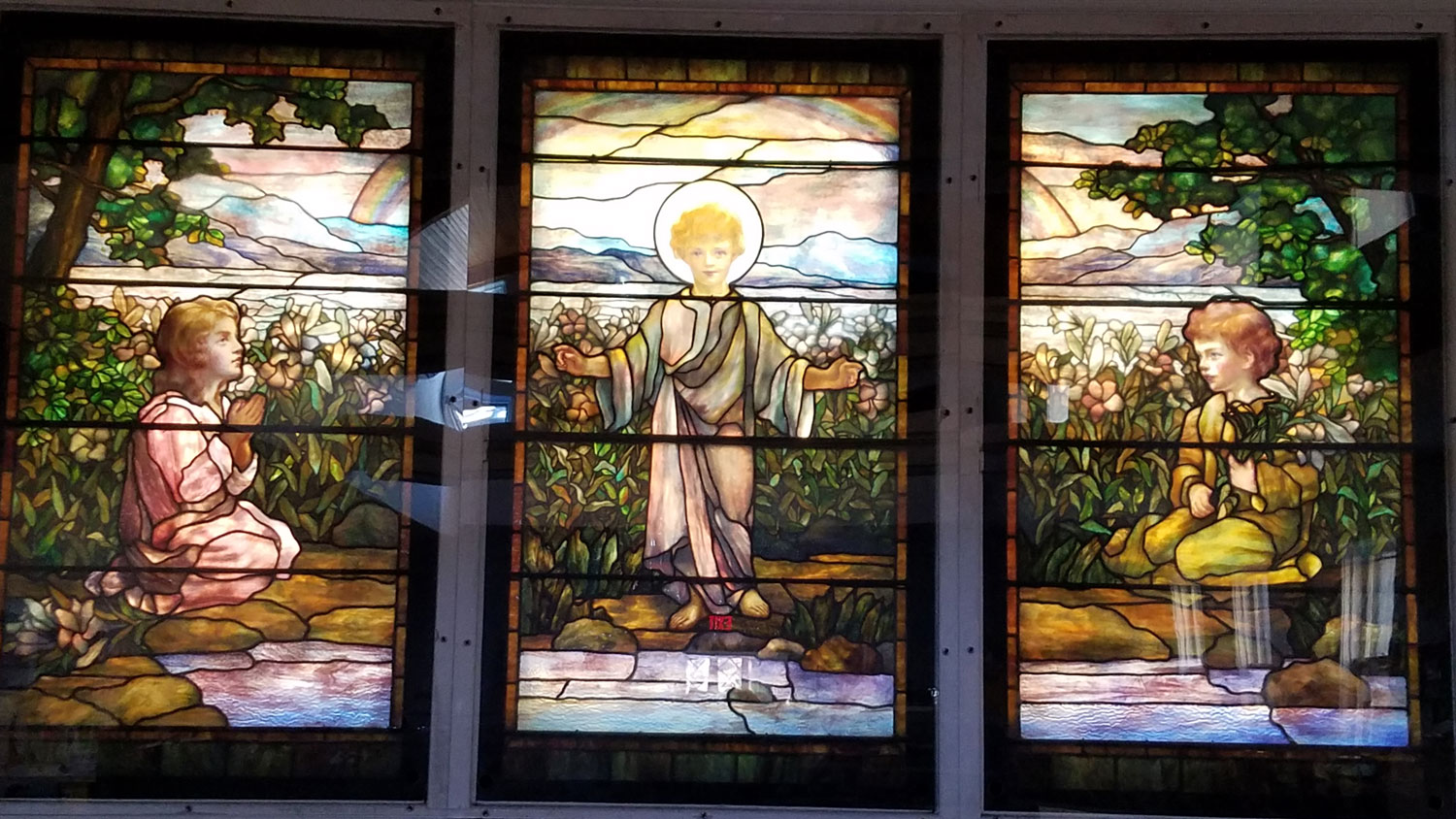 Five beautifully rendered Tiffany windows light Penson Hall/Child Care Center. Adoring angels flank the center panels, two children adoring the young Jesus. The models for these faces were Katherine MacKay's children - Katherine, Ellin and John.